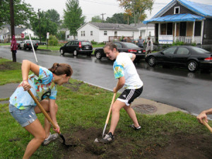 "SyracuseCoE staff members Tara Nelson (left) and Suzy Englot -- members of ""Team SyracuseCoE"" -- dig out a flower bed on Ontario Street."