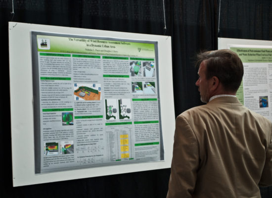 Photo of Symposium Attendee Interacting With Student Poster