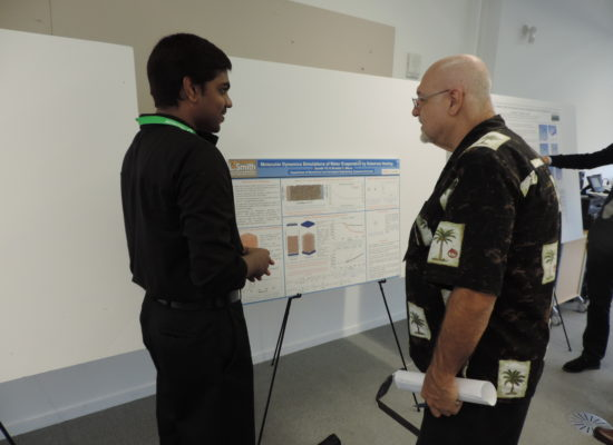 Photo of Student Describing Poster to Symposium Attendee