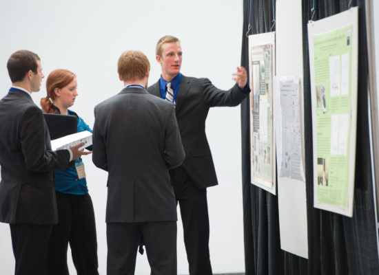 Photo of Student Presenting Poster and Findings