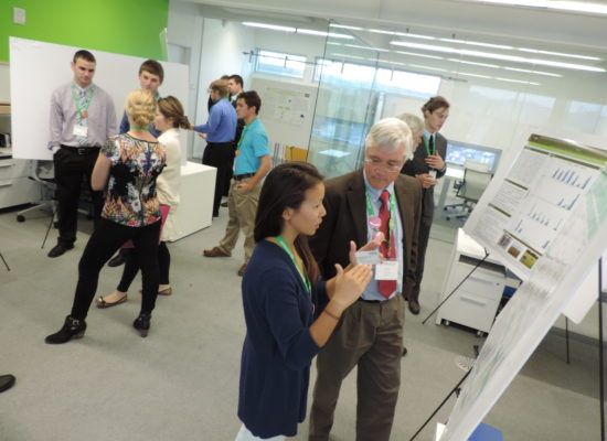 Photo of Students Explaining Research Findings to Symposium Attendees