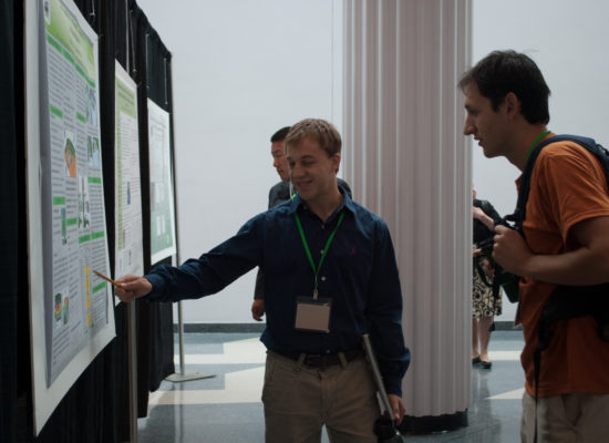 Photo of student presenting his research poster to Michael Amidon