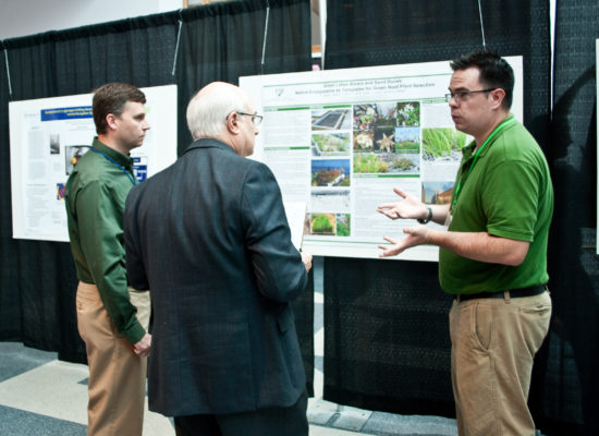 Photo of Bob Delzoppo judging a poster presentation