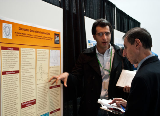 Photo of Cliff Davidson judging a student researchers poster